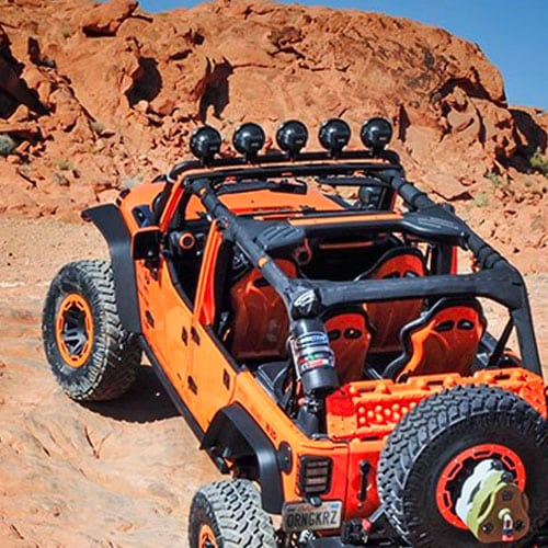 An orange off-road vehicle coated with bed liner paint in the tub, grille, and other areas