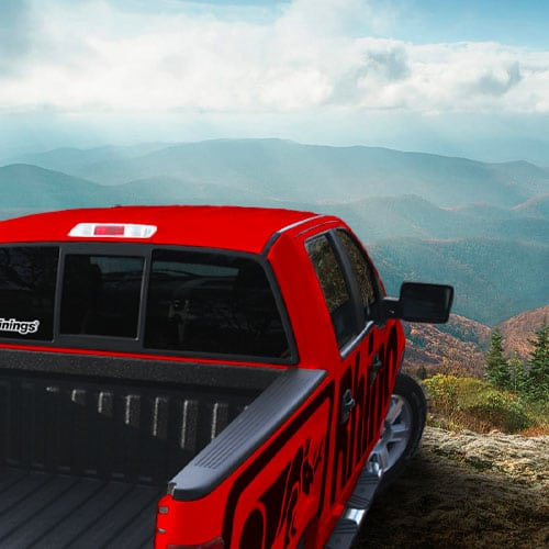 A red truck with the logo for Rhino Linings on the side looking out over a mountain view