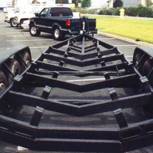 A boat trailer that has been coated with black Rhino Linings spray